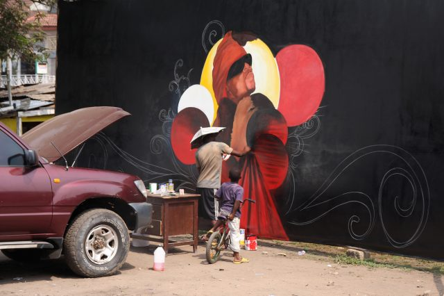 Accra, Ghana - December 24, 2008: Street artist making a picture for celebrating Christmas eve the same day later.