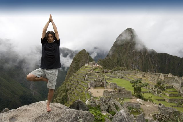 A male tourist does the tree yoga pose at the ancient historical Inca city of Machu Picchu in Peru. Wide angle view.