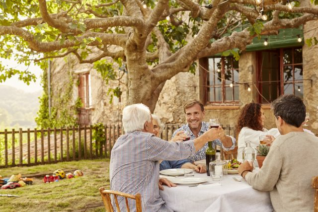 Family toasting wineglasses at table. People are enjoying outside house. They are resting in yard.