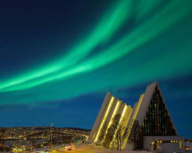 Illuminated Tromso cathedral at night with beautiful green shapes of aurora borealis