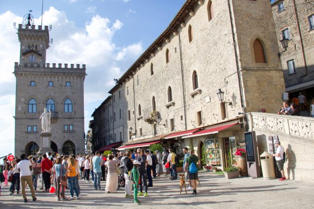 Italy- Città di San marino - May 13, 2018: group of tourists in the capital city of Republic of San Marino in the freedom square with the public palace called also Palazzo del Governo
