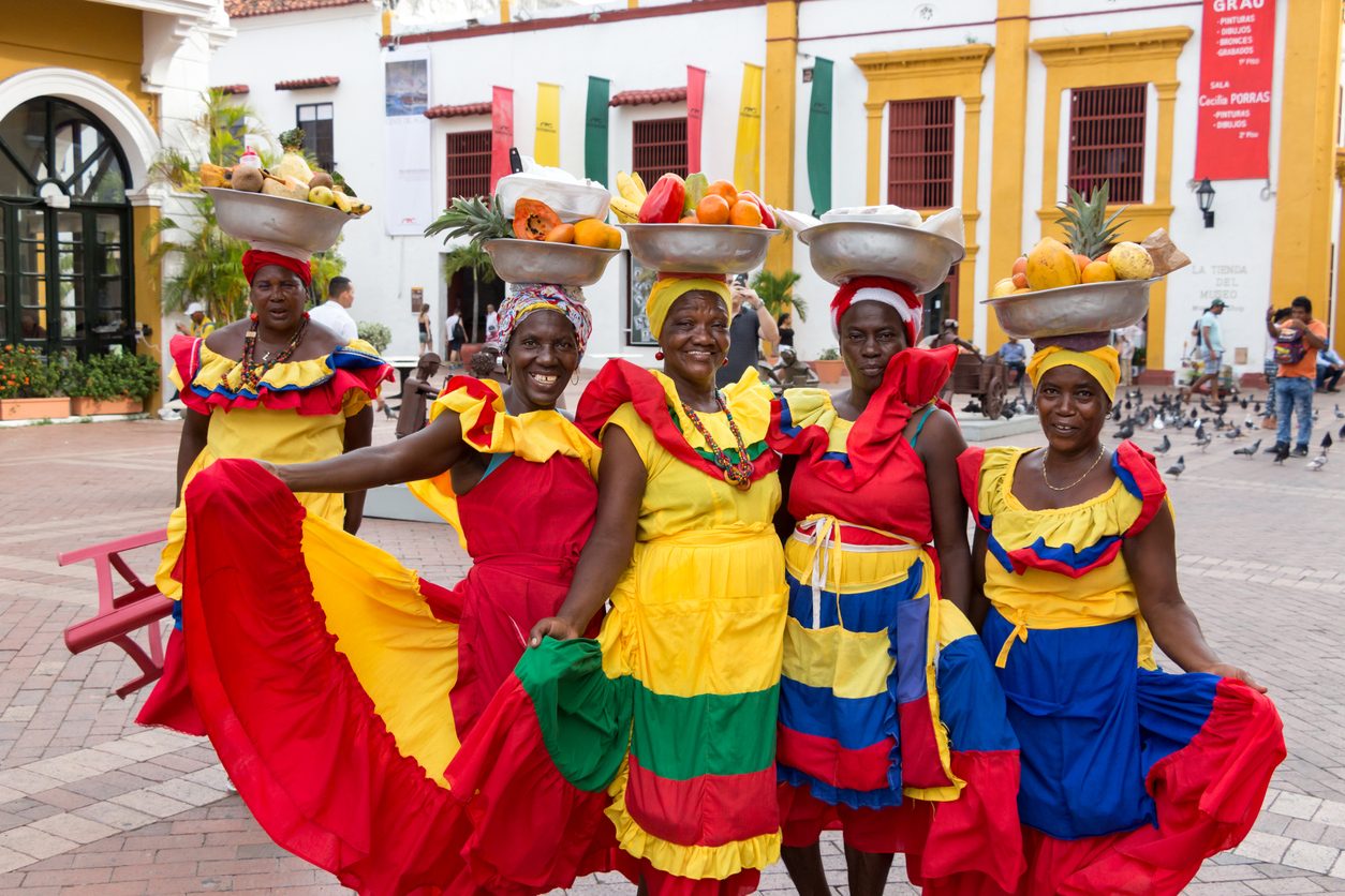 Cartagena: Five palenqueras with a metal basket with fruits are posing showing their multicolor traditional dress at the old town of Cartagena de Indias.