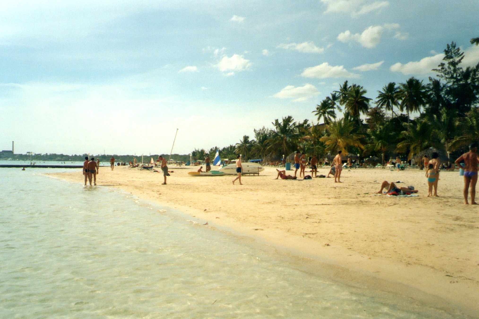 Boca Chica, Dominican Republic - February 21, 2006: Tourists relaxing on the white sandy beach surrounded by palm trees at Boca Chica, along Dominican Republic southern coastline