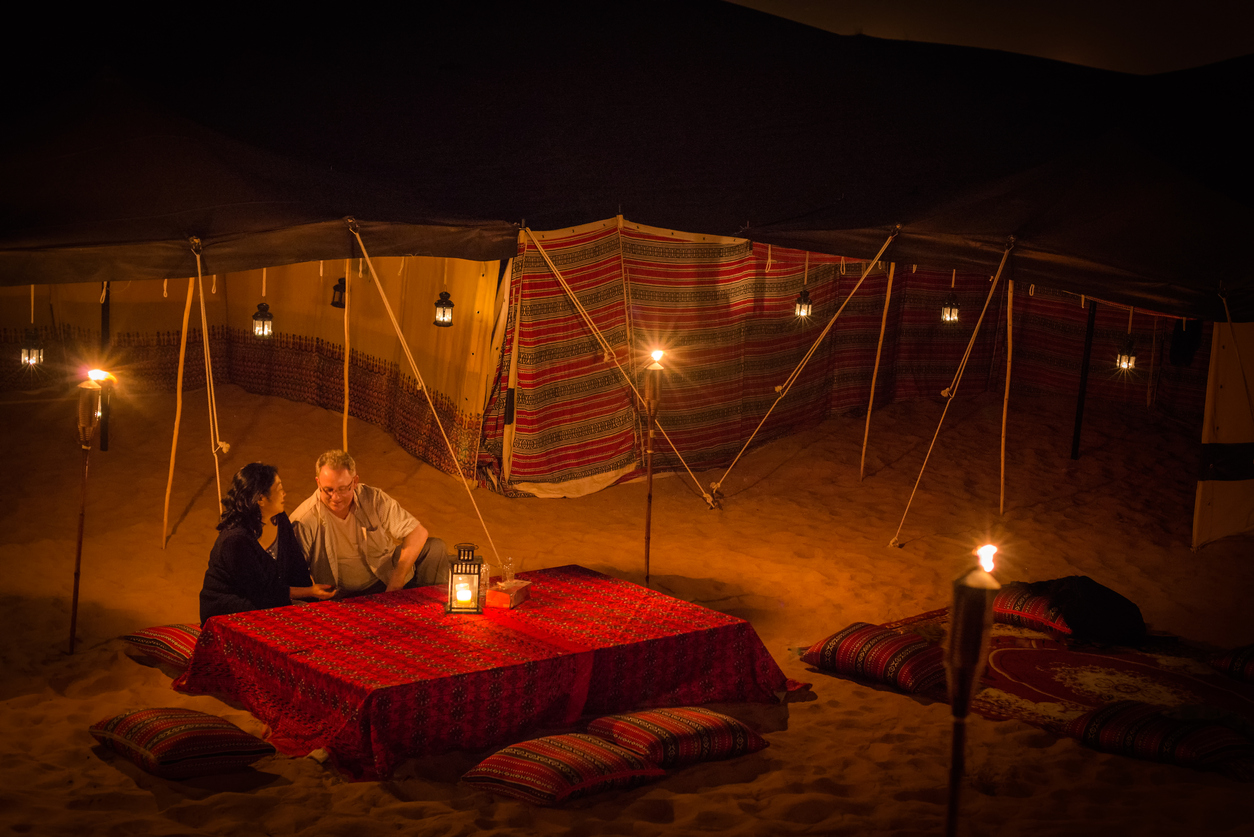 Dubai iStockalypse. A mature, multi-ethnic couple enjoy a private, luxury, traditional Arab, Middle Eastern camp in the red desert between Dubai to Sharjah, United Arab Emirates. The desert camp is lit by candles, lanterns, and torches amid the tents in the sand dunes and is decorated with traditionally patterned pillows, fabrics, carpet and tablecloth.