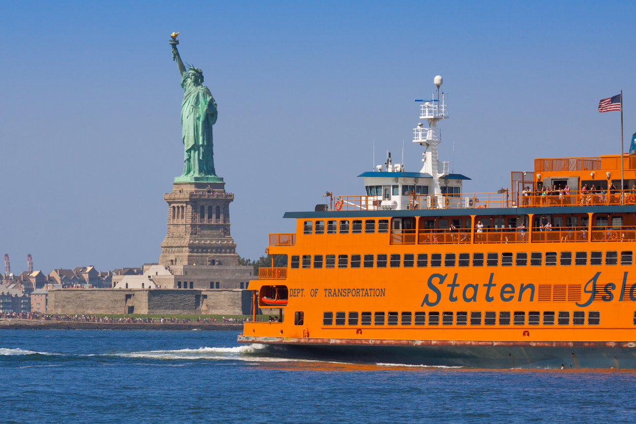 New York, NY, USA - August 25, 2014: Staten Island Ferry and The Statue of Liberty, lit by morning sun. Commuters on the ferry enjoying beautiful summer morning. Middle part of hte statue is slightly distorted by the hot exhaust from the ferry. Canon EF 70-200mm f/4L IS lens.