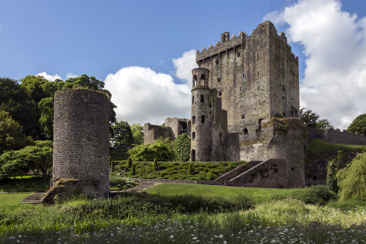 Cork, Ireland - June 12, 2016: Blarney Castle is a medieval stronghold in Blarney, near Cork, Ireland. The castle originally dates from before 1200, when a timber house was believed to have been built on the site, although no evidence remains of this. Around 1210 this was replaced by a stone fortification. This was destroyed in 1446, but subsequently rebuilt. The Blarney Stone is a block of limestone built into the battlements of Blarney Castle. According to legend, kissing the stone endows the kisser with the 'gift of the gab' (great eloquence, clever, or flattering talk). The castle is open to the public and run as a tourist attraction by the MacCarthy family, and Hollow Sword Blade Company.