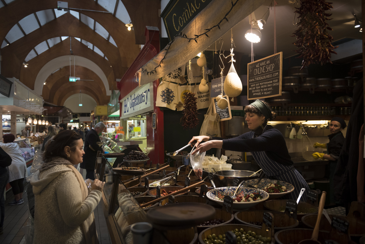 A woman serves food to a customer at the English Market, a municipal food market in the city center of Cork, Ireland. (April 24, 2018)