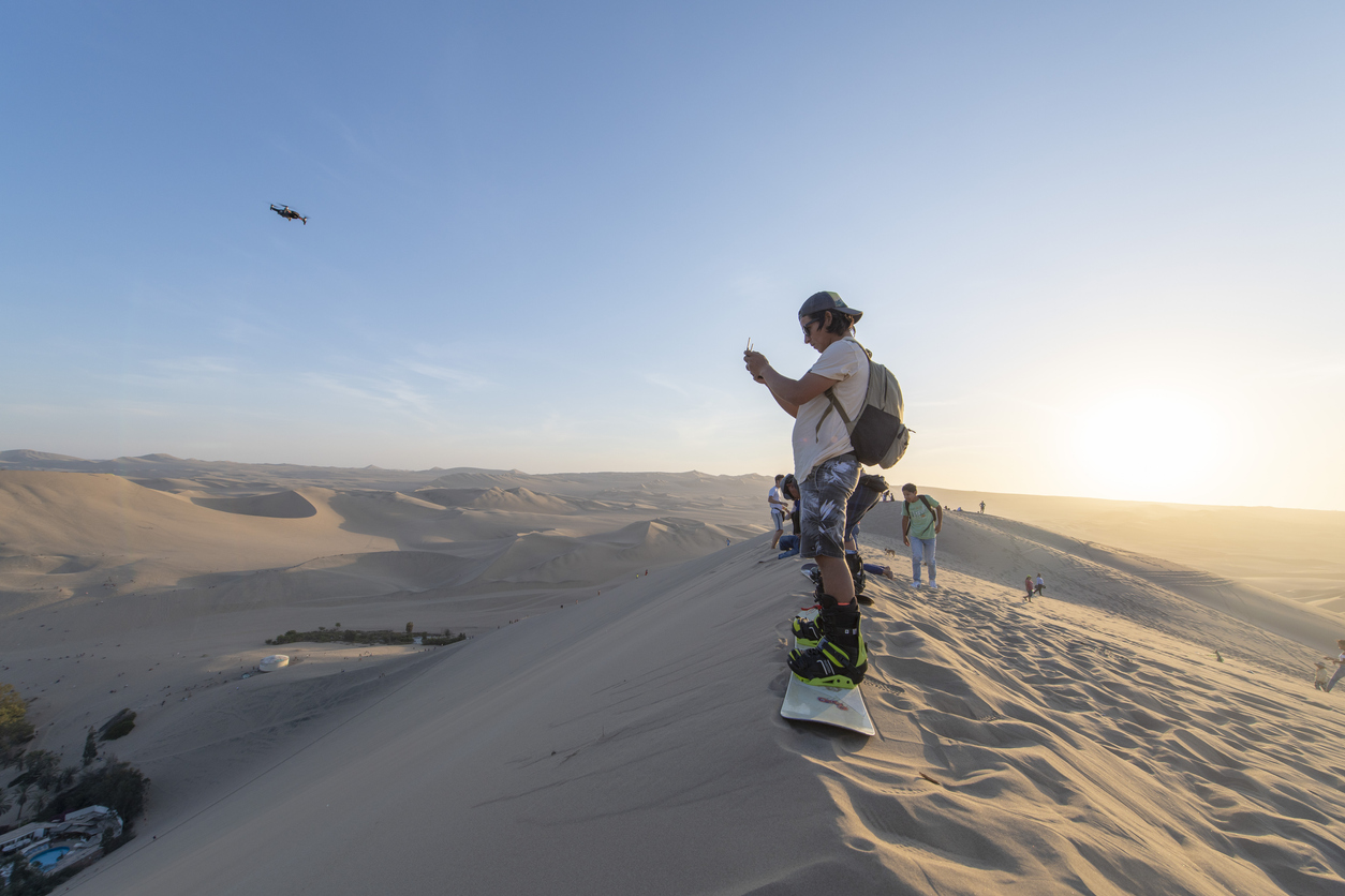 People sandboarding and flying drone in the desert of Huacachina in Peru, during the late afternoon in the summer.