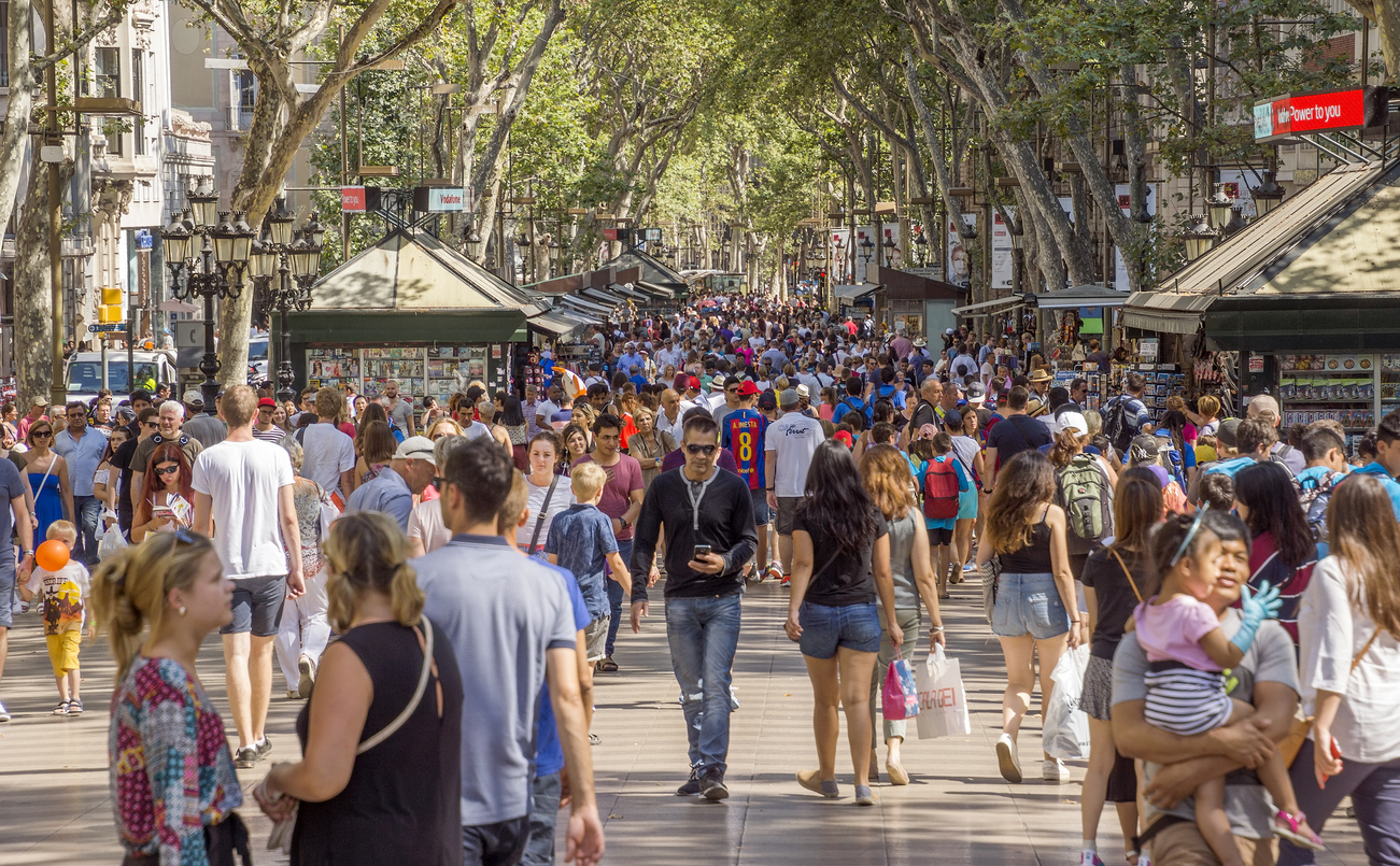 Barcelona, Spain - July 5, 2016: Hundreds of people promenading in the busiest street of Barcelona, the Ramblas. The street extends 1.2 kilometers connects the Placa de Catalunya in the centre with the Christopher Columbus Monument at Port Vell.