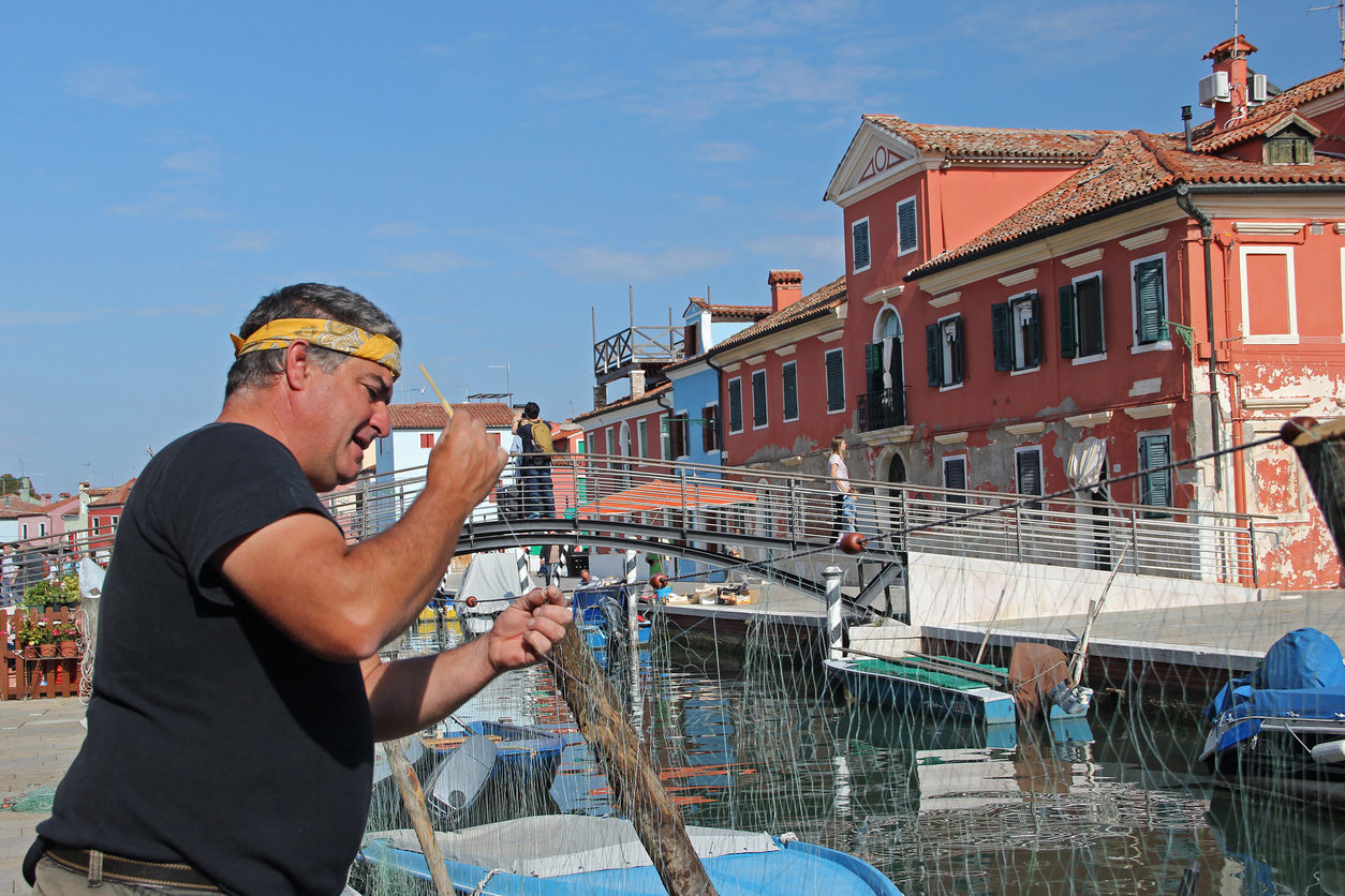 Venice, Italy - October 3, 2014: Middle aged Fisherman is repairing fishing net near Venice sea canal. In the background colorful hauses of fish and touristic village on Burano island in Venice, Italy.