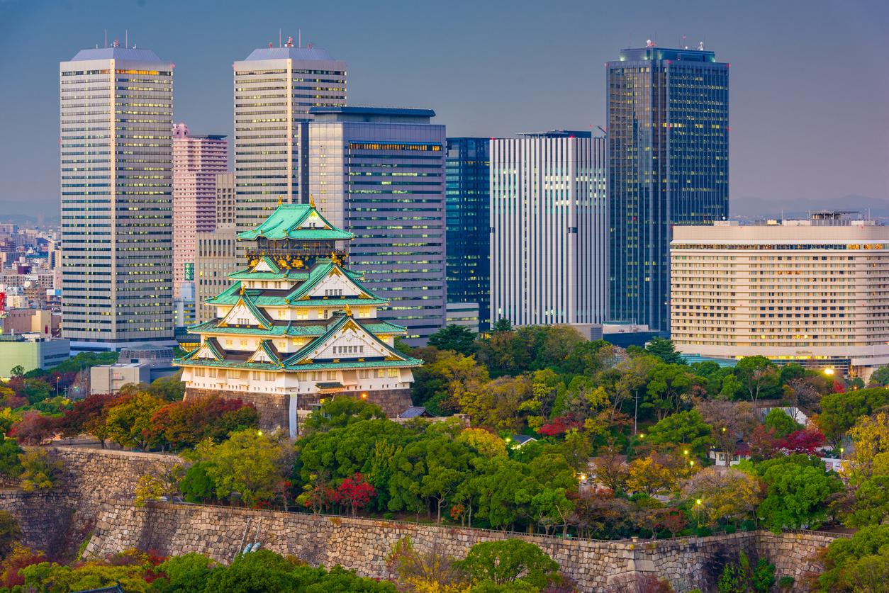 Osaka, Japan - November 20, 2015: Osaka Castle stands against the skyline of Osaka Business Park during the autumn season.
