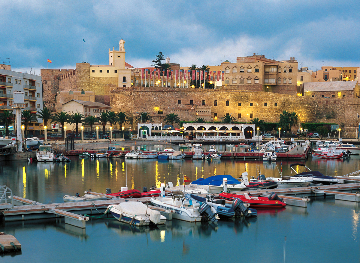 Sunset view of Sailing boats moored at the harbor of Melilla with the Old city Fortress at the back.