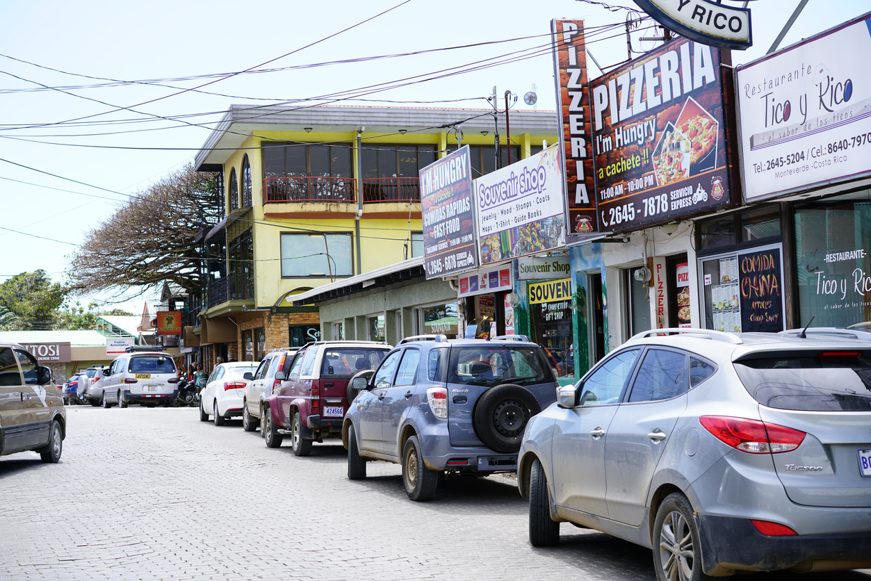 Santa Elena, Costa Rica - February 02, 2017: A lot of cars parked on the street of small mountain town Santa Elena in region of NP Monteverde, Costa Rica. In background are buildings with billboards with different information for restaurants, stores and for activities what can be done in area, which is one of most famous tourist destinations in Costa Rica. Town is starting point for many different activities like canopy, Cloud Forest, horse riding and visiting coffee plantations.