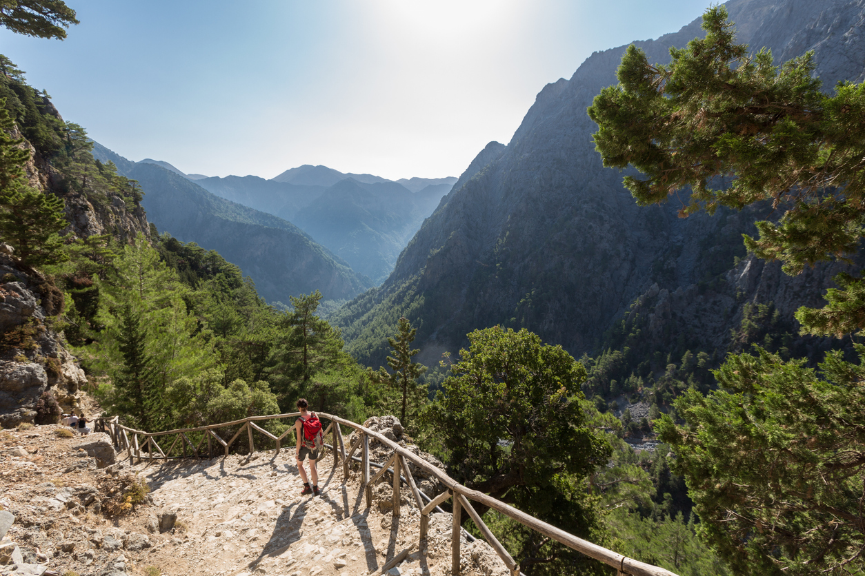 A woman on her way down to the entrance of Samaria Gorge, Crete. The gorge is in southwest Crete in the regional unit of Chania and a major tourist attraction of the island. It was created by a small river running between the White Mountains and Mt. Volakias. The gorge is 16 km long, starting at an altitude of 1,250 m (4100 ft.)at the northern entrance, and ending at the shores of the Libyan Sea in Agia Roumeli.