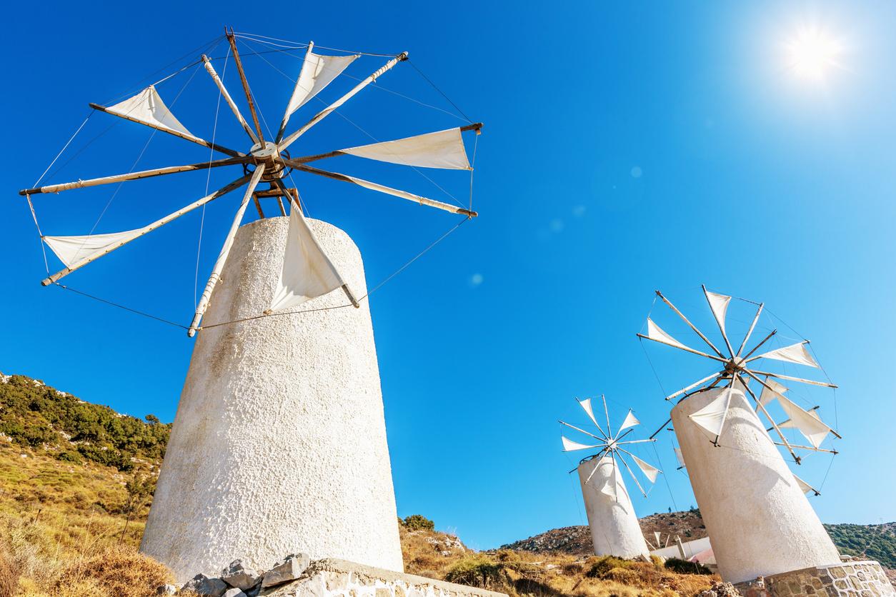 Windmills upon a hill against light blue summer sky.
