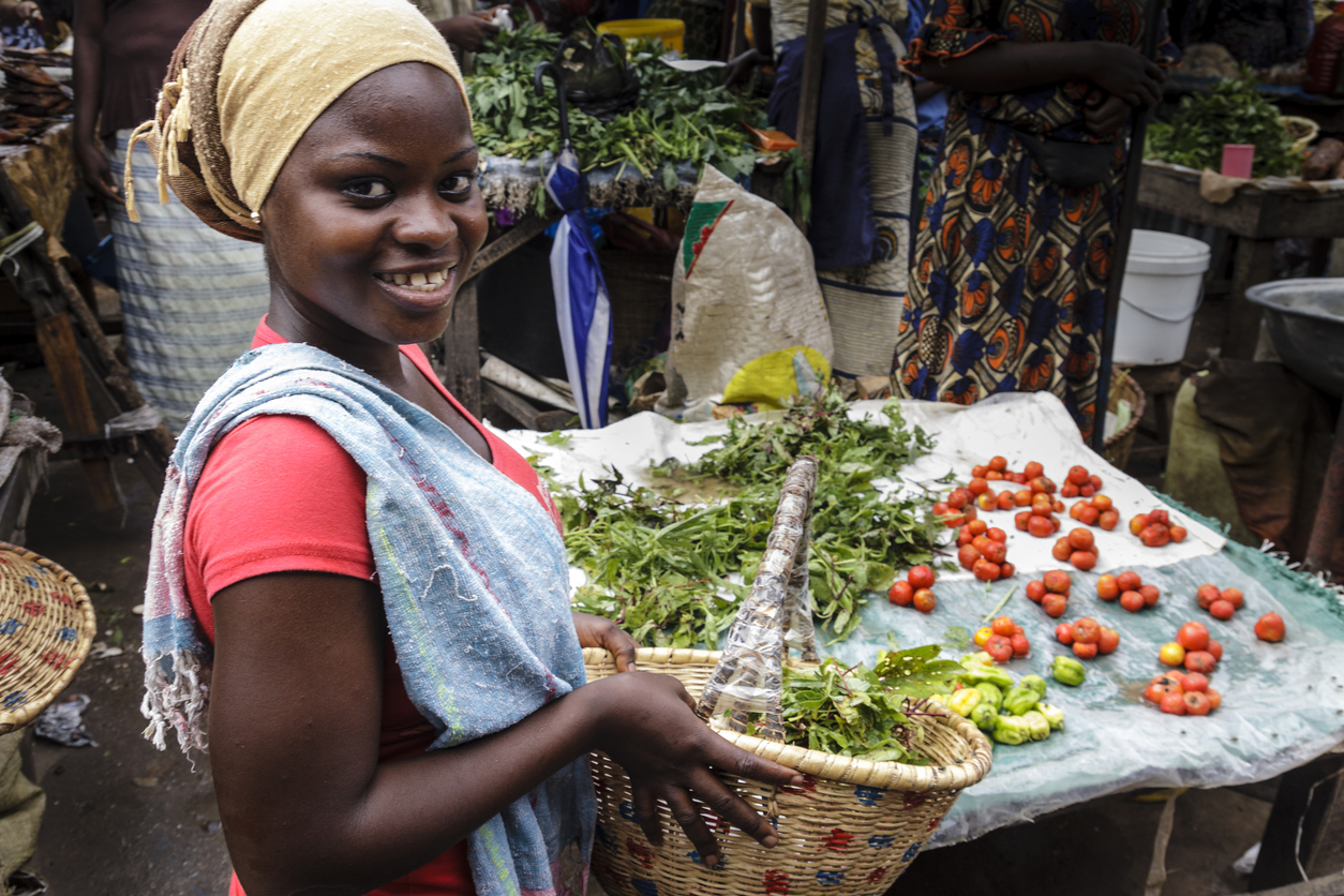 Woman showing the basket of the purchase on the market of Zidanchor's African city, Senegal