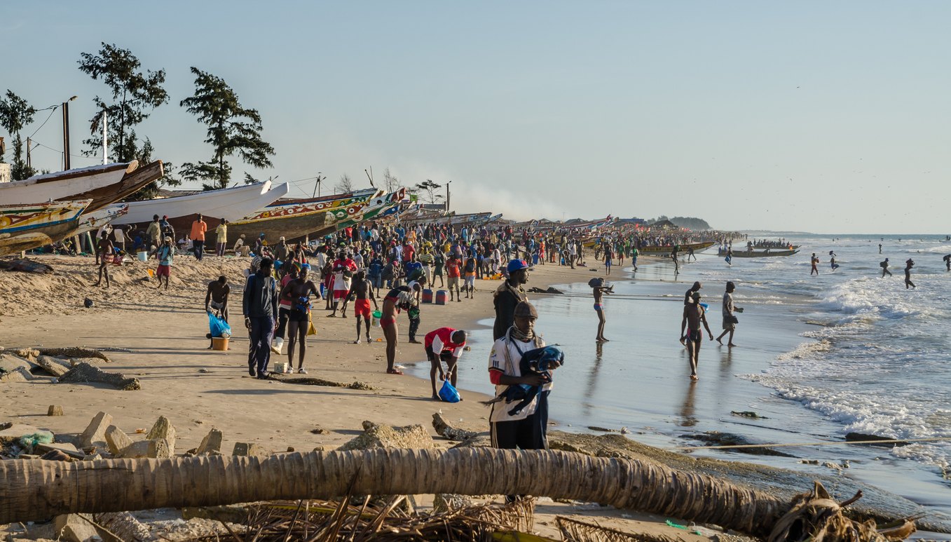 Kafountine, Senegal - November 26, 2013: Return of the fishermen in wooden boats at beach in Casamance with many locals loading and unloading and waiting on the beach