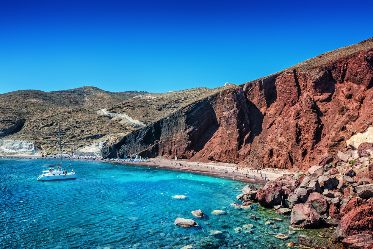 Red Volcanic Beach with on Santorini. Beautiful summer day with clear sky over the Turquoise Water on Santorini, Greece.