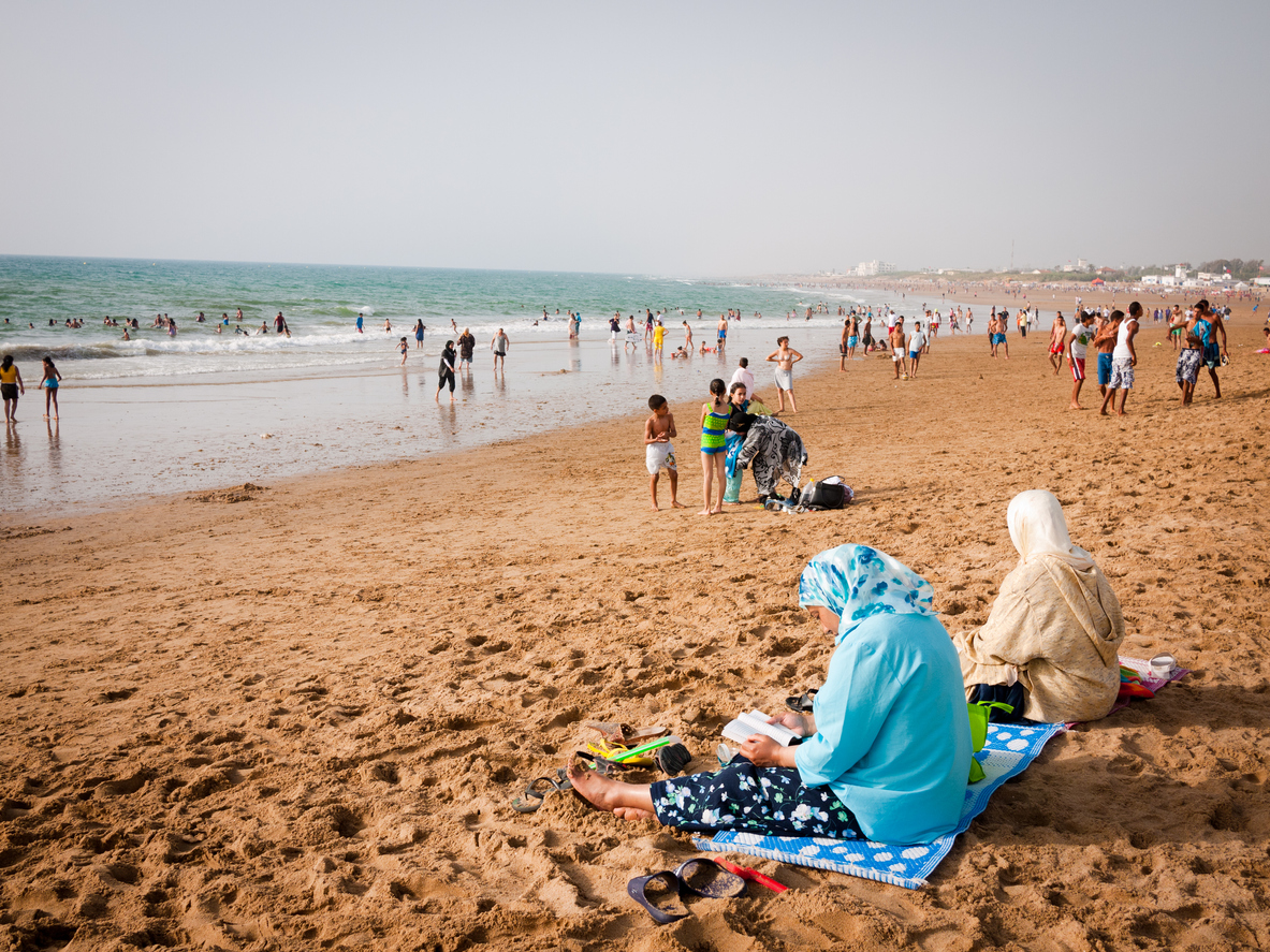 Asliah, Morocco - July 9, 2010: Moroccan woman wearing headscarves sit on the beach in the late afternoon with other locals playing in the background