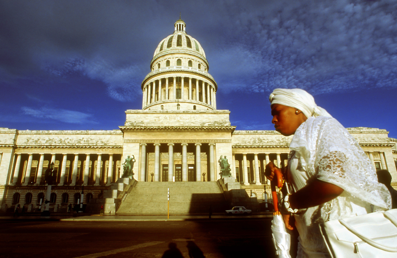 Woman santera passing the Capitolio Nacional, Havana, Cuba. Santería, also known as Regla de Ochá or La Regla de Lucumí is a syncretic religion of Caribbean origin which developed in the Spanish Empire among West African slaves. Santería is influenced by and syncretized with Roman Catholicism. Its liturgical language, a dialect of Yoruba, is also known as Lucumí.
