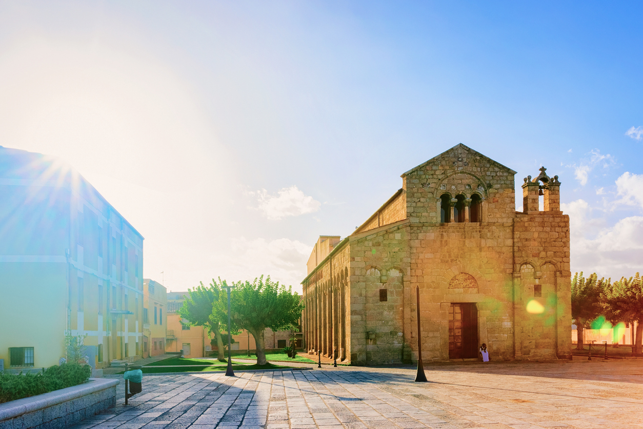 Basilica di San Simplicio Church in Old city of Olbia on Sardinia Island in Italy. Square with street lanterns and Cathedral in Sardegna island. Blue sky and sunlight