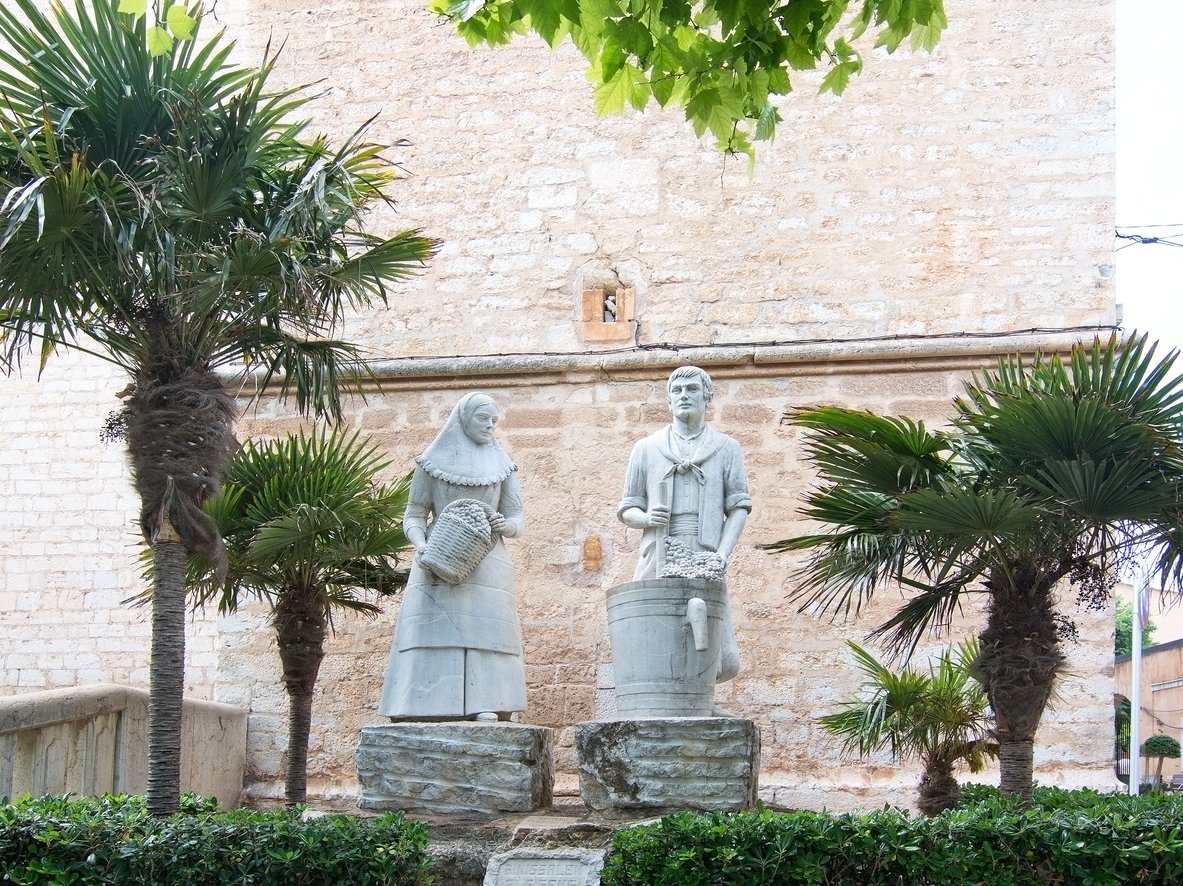 Binissalem, Mallorca, Balearic islands, Spain - May 19, 2016: Man and woman winery workers stone sculpture against traditional stone wall with palm trees.