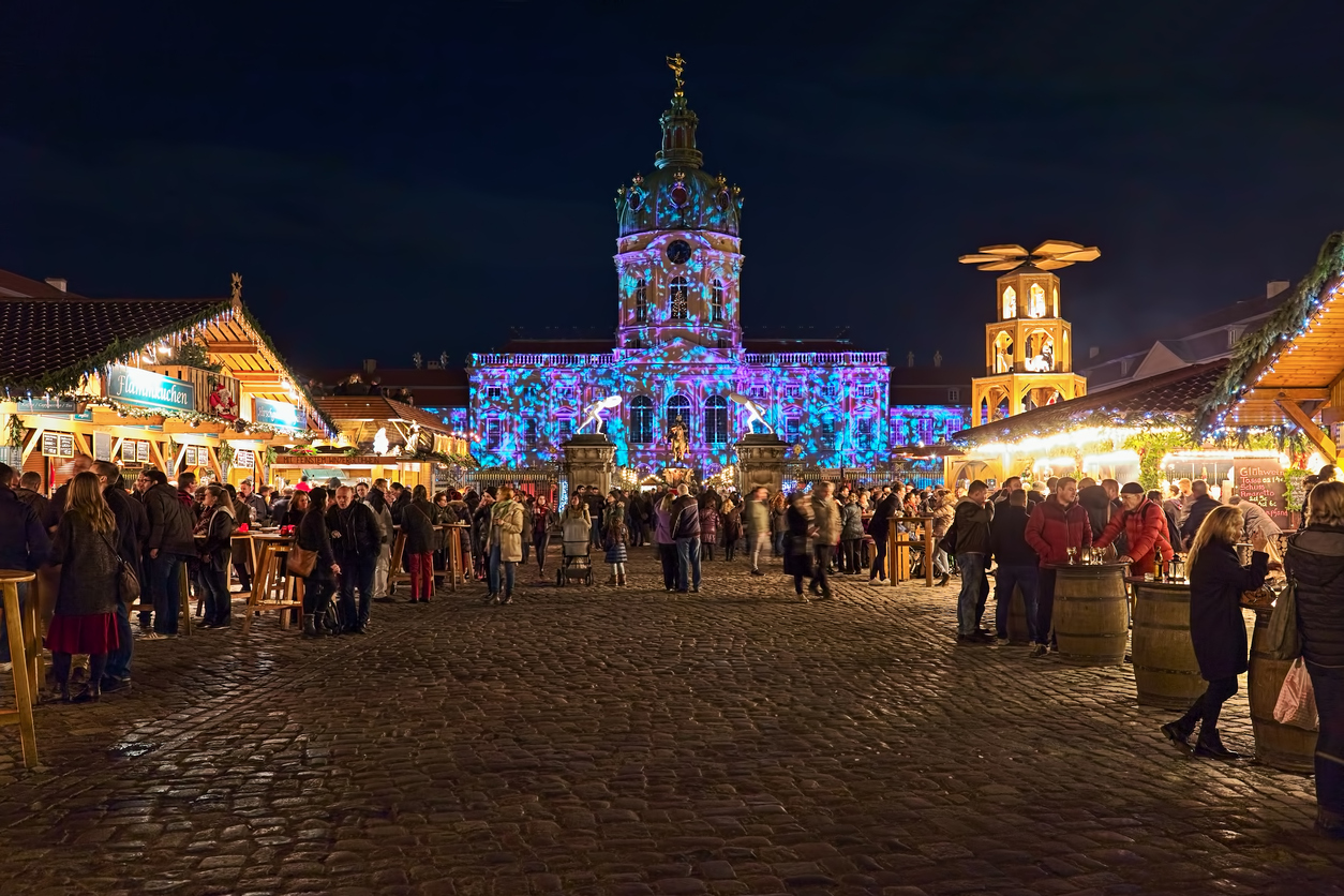 Berlin, Germany - December 3, 2018: Christmas Market in front of the famous Charlottenburg Palace in night. Unknown people walk around the market stalls and consume food and drinks. Facade of the Palace is illuminated with Christmas lights show.