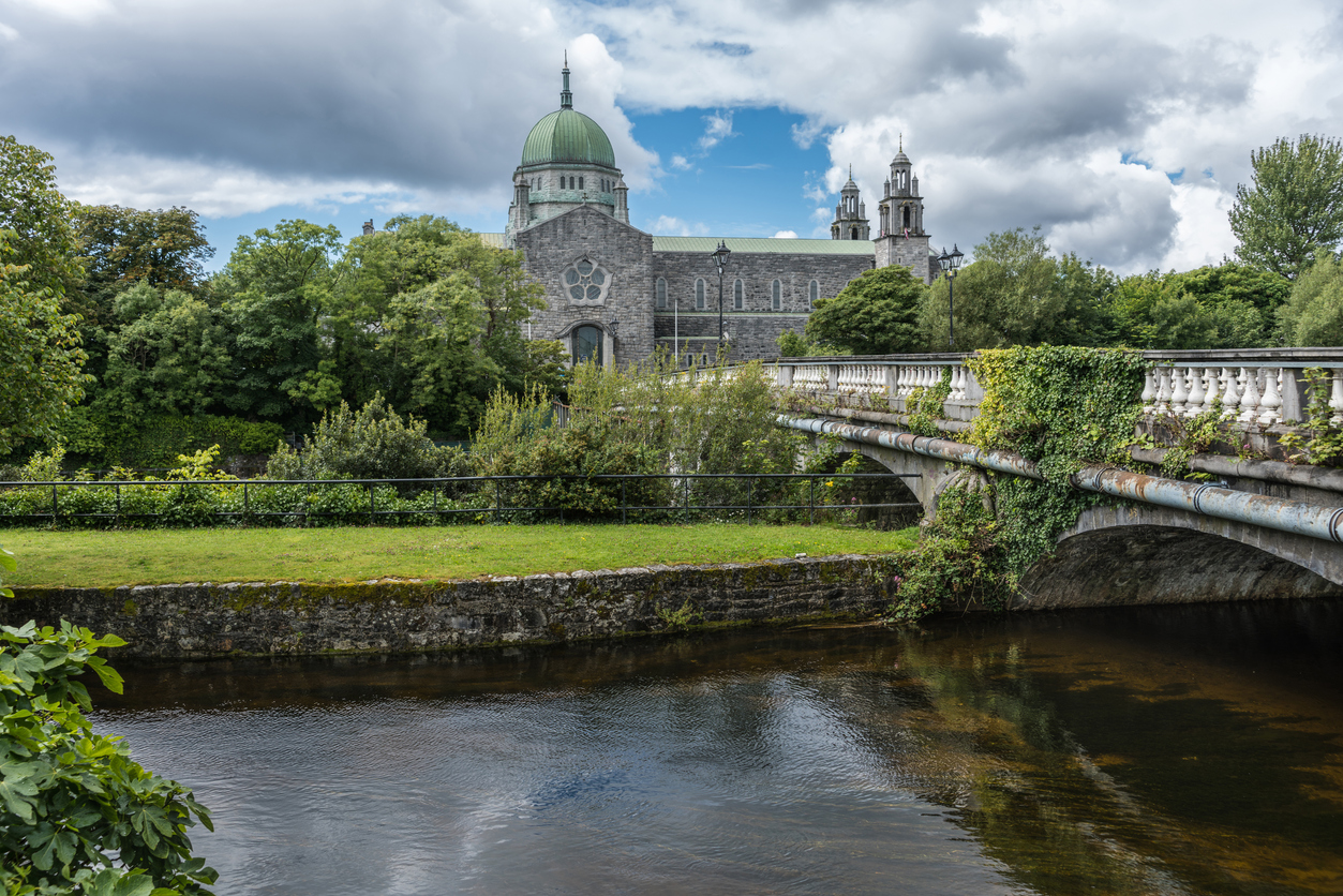 Galway, Ireland - August 5, 2017: The Cathedral building with dome and Salmon Weir Bridge leading to it. Under cloudscape seen from across Corrib River. Lots of green trees.