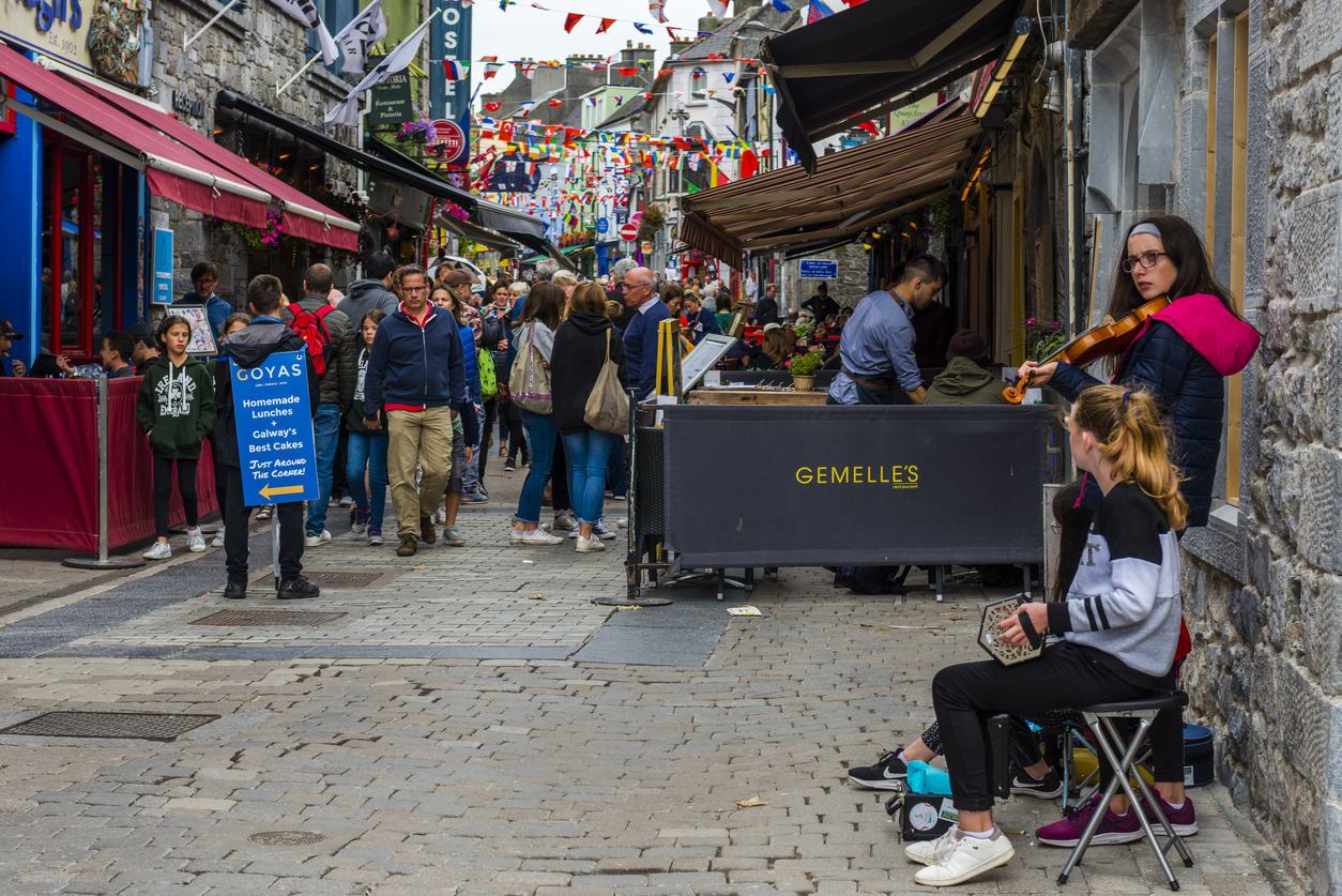 Galway, Ireland - August 07, 2018: People walking along one of the main pedestrian streets in Galway. It is full of shops, pubs and restaurants. Street musicians are performing.