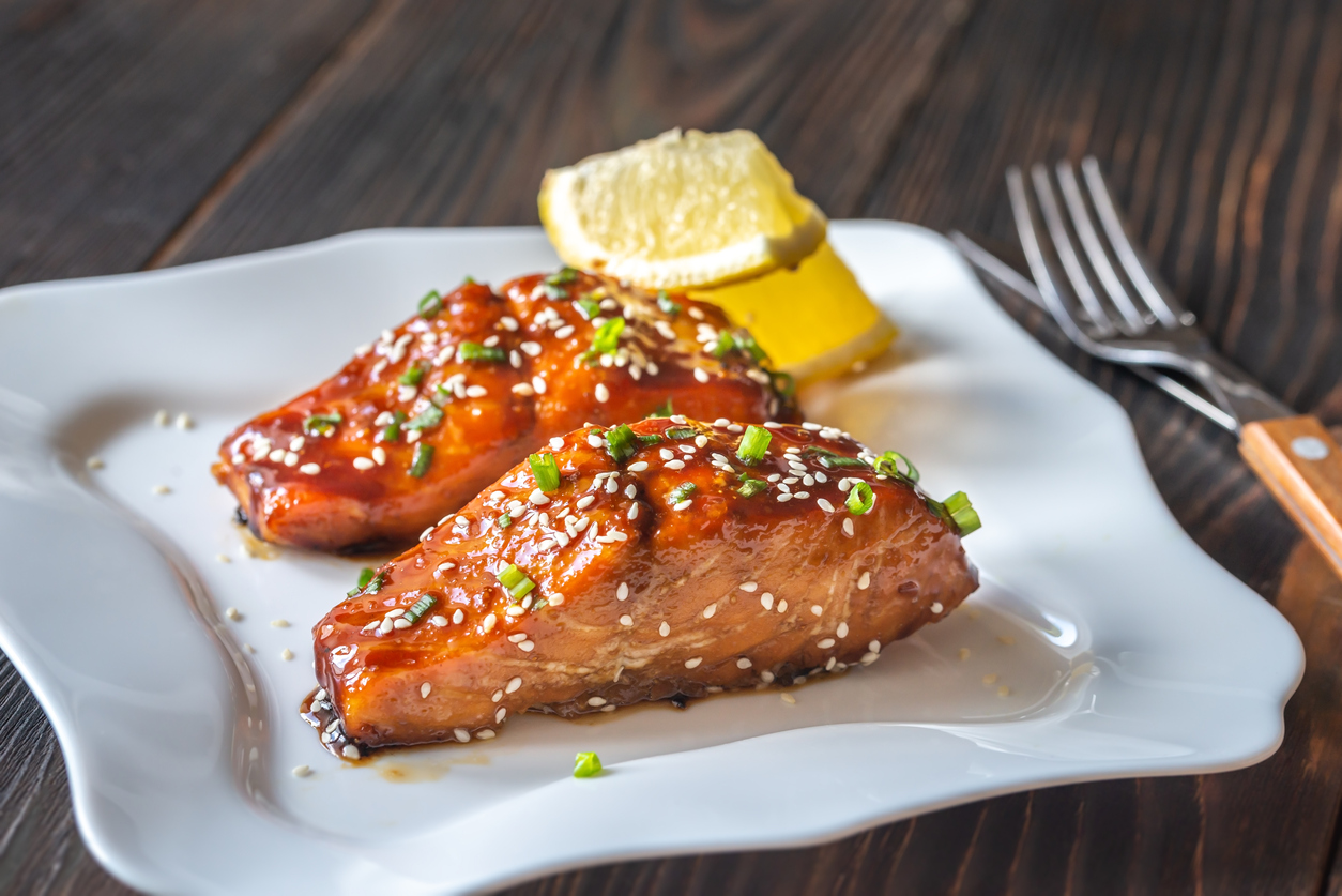 Two pieces of teriyaki salmon garnished with sesame seeds and spring onion
