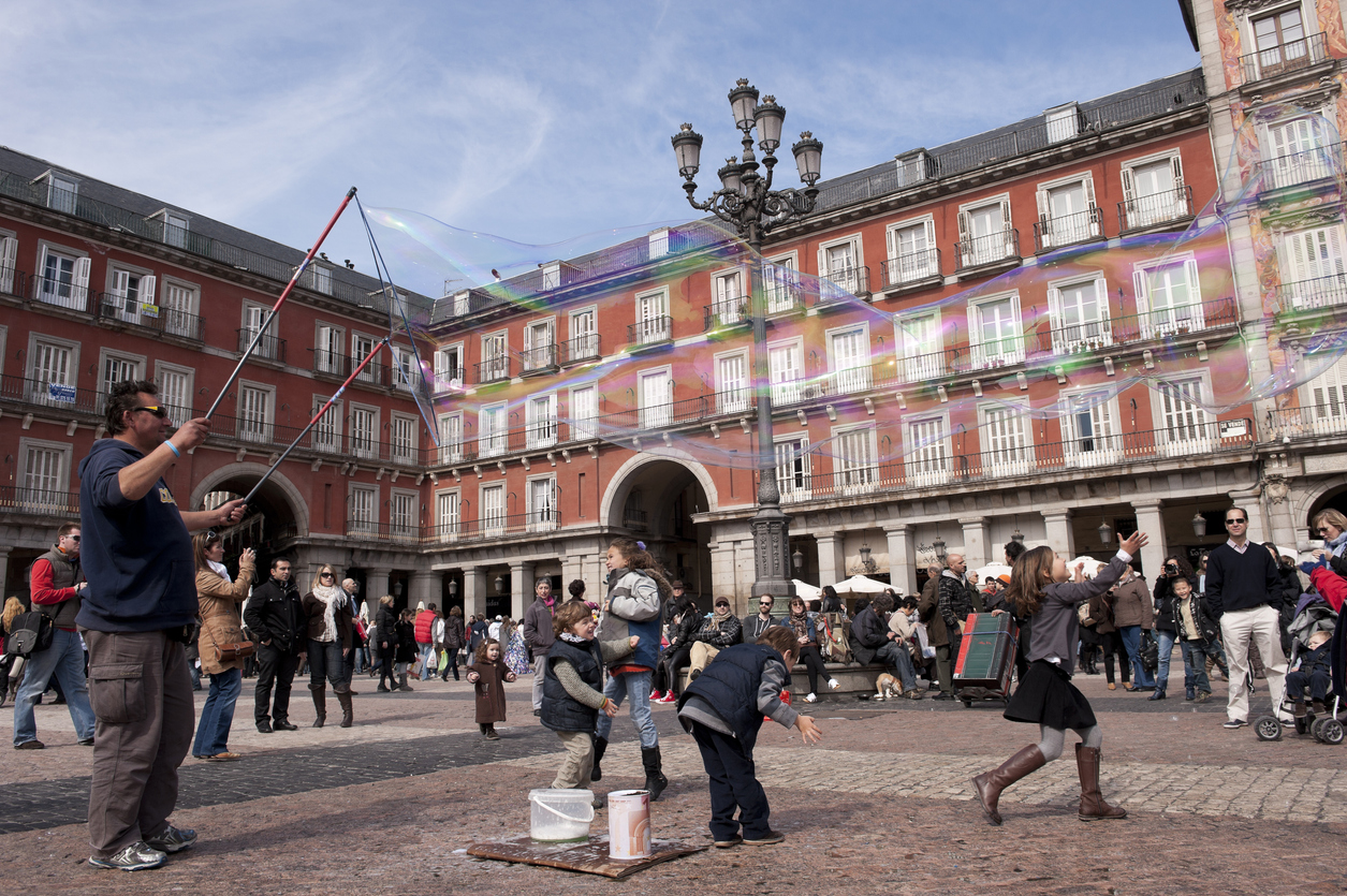 Madrid,Spain - March 6, 2011: Person making soap bubbles and playing with Them children, while other tourists in the background, visit the Plaza Mayor in Madrid, one of the tourist sites of the capital of Spain.