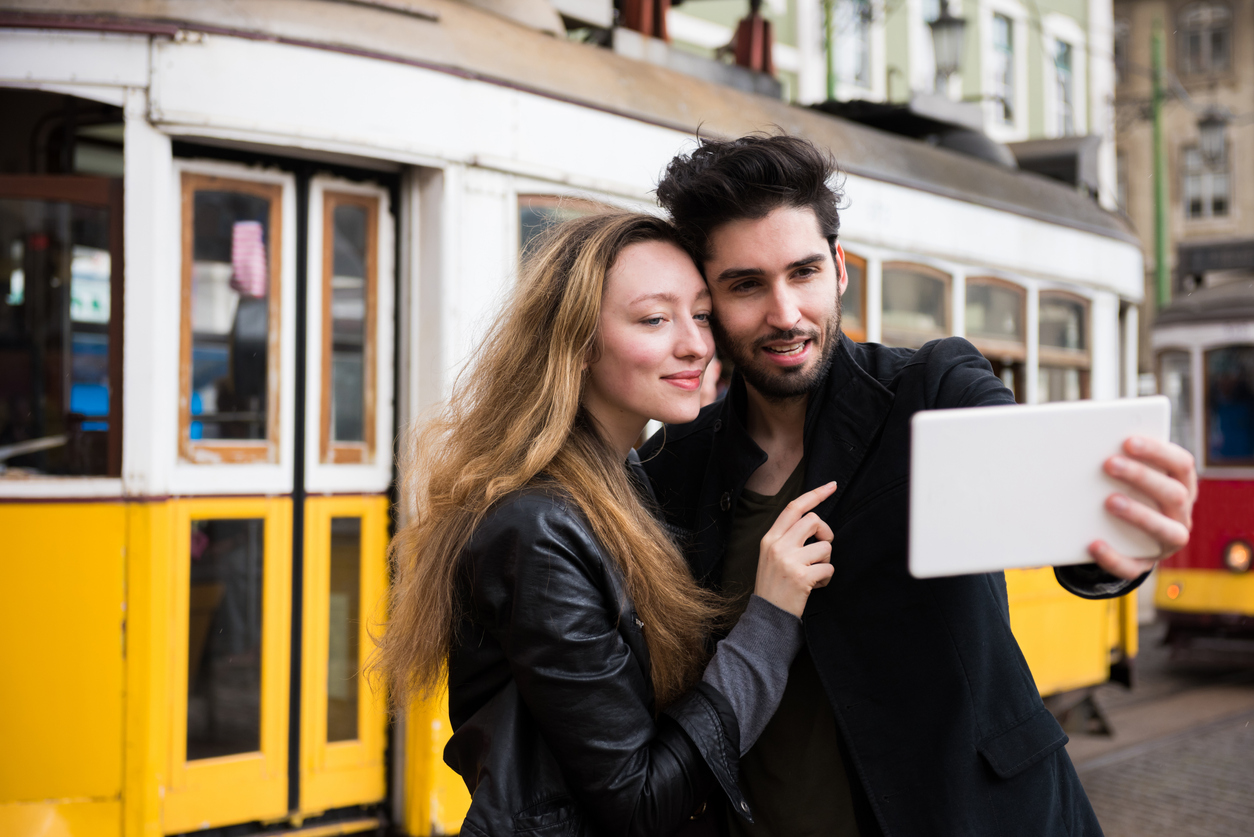 Tourist couple taking a selfie with a digital tablet in front on a vintage tram on vacation