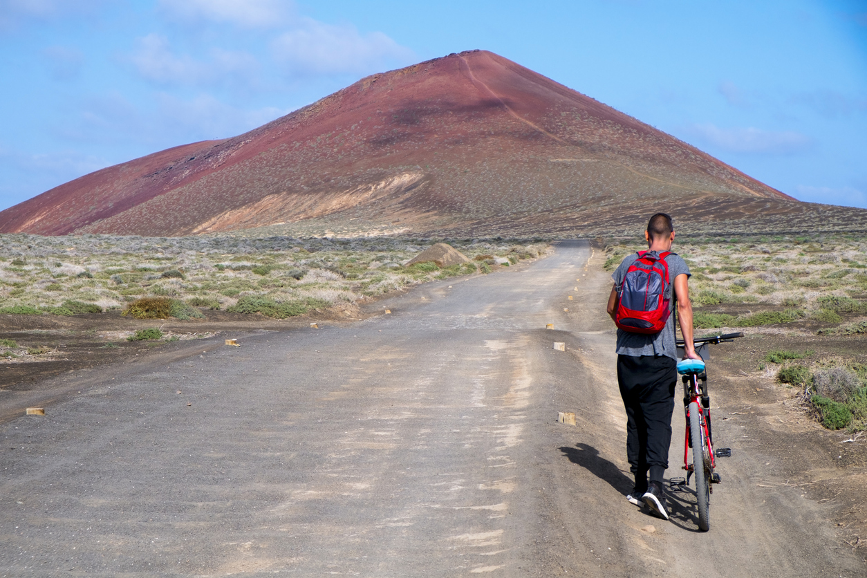 a young man seen from behind carrying a bike by the handlebar in a dirty road in La Graciosa, Canary Islands, Spain