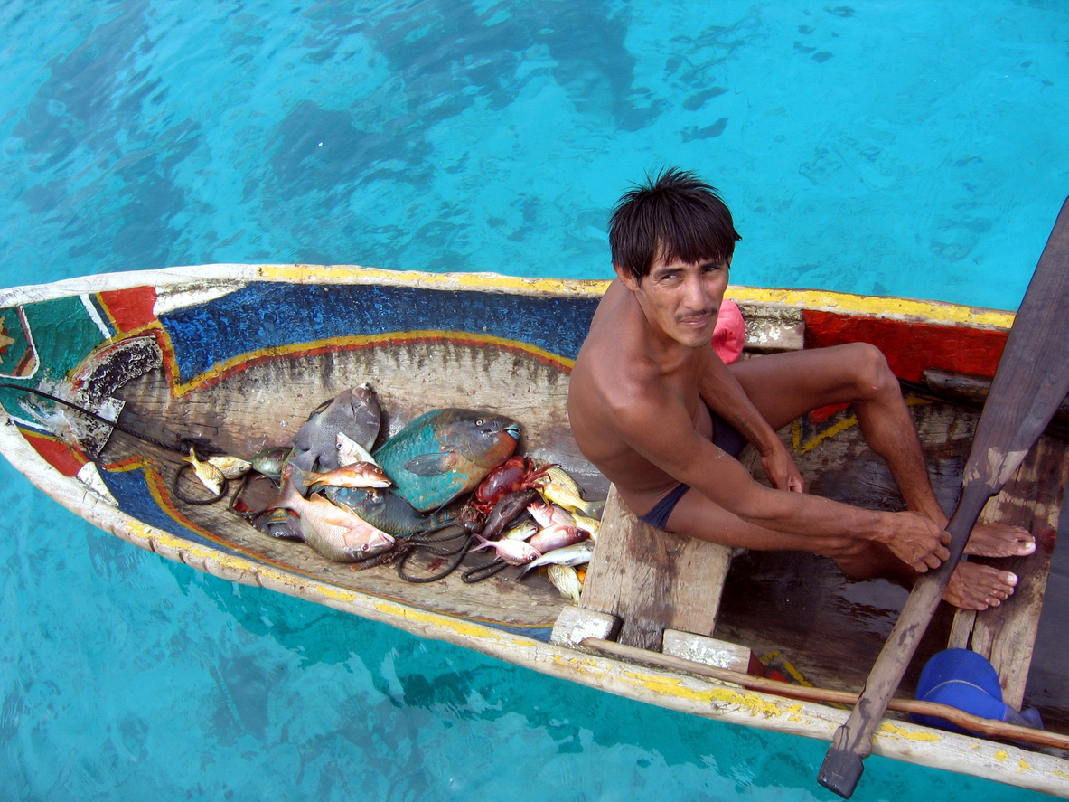 San Blas Islands, Panama - June 3, 2005: Kuna indian sitting in his canoe on the sea tries to sell his fish on a weekday.