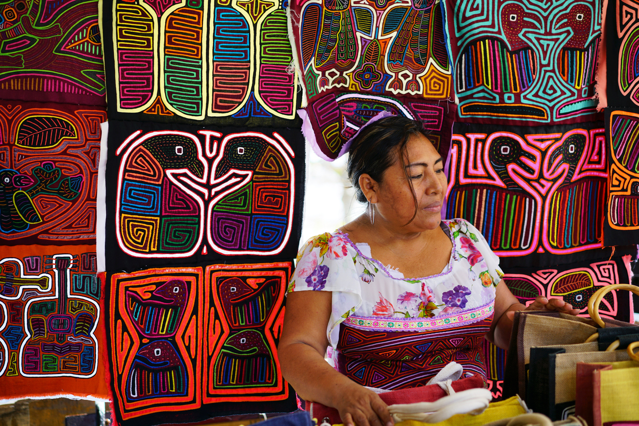 Panama City, Panama - February 12, 2017: Kuna Yala woman in very traditionally colorful clothes selling souvenirs from her kiosks, mostly for tourists. The kiosk is in Casco Viejo an old part of Panama City. Kuna Yala tribe belongs to indigenous people living on san Blas islands and their handcraft is most famous in Panama.
