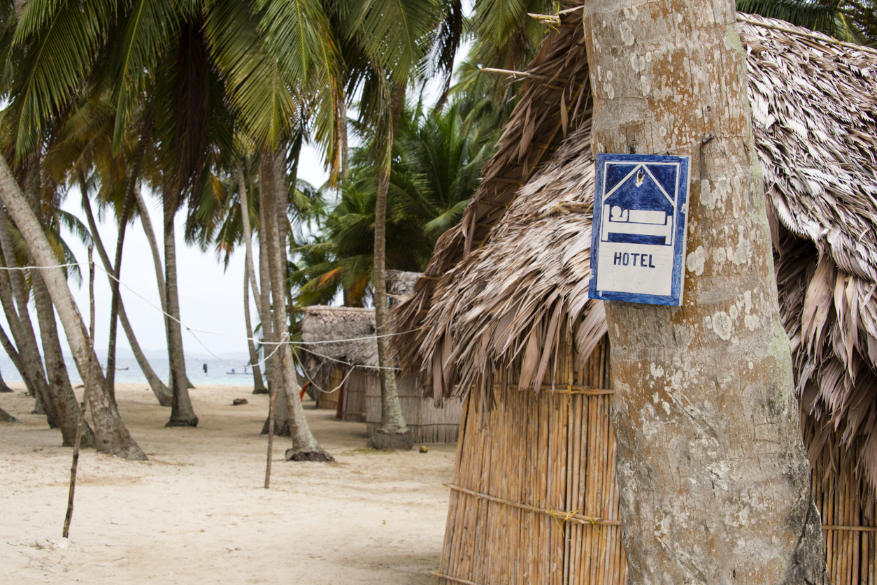 Hotel sign on a tropical island with simple bamboo huts covered with palm leaves.