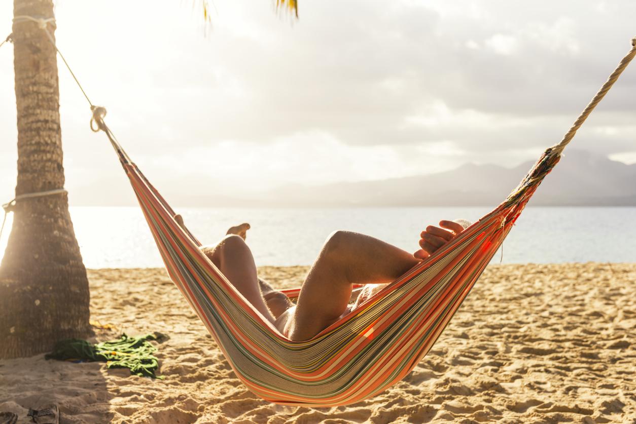 Senior man sunbathing in hammock tied on palm tree on the sandy beach. Sun Blash islands, Panama.
