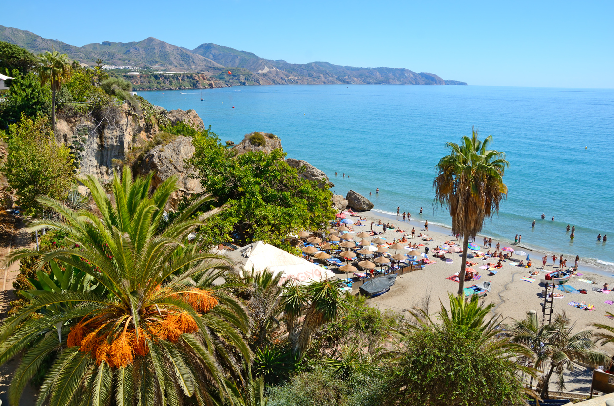 Nerja, Spain - September 18th, 2016: Coastline in Nerja, famous resort in Costa del Sol, called Balcon de Europe. Mediterranean sea on the right. Sierra Nevada mountains on the horizon. In the foreground on right a little beach with straw sunshades and many people. In the foreground on the left rocks ovegrown with many bush and a date palm. Horizontal image in a sunny day.