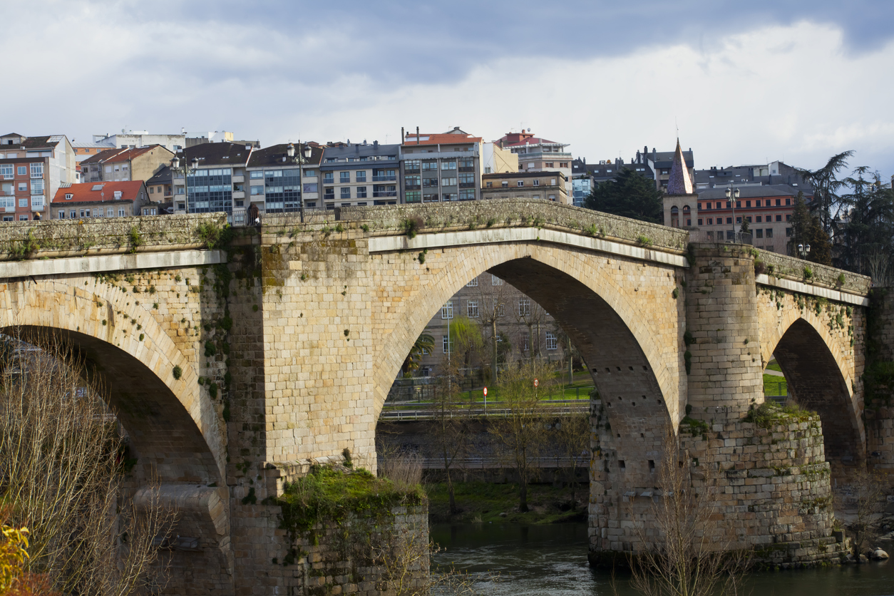 Roman bridge in Ourense (Galicia, Spain), over river Miño and city scape in the background..
