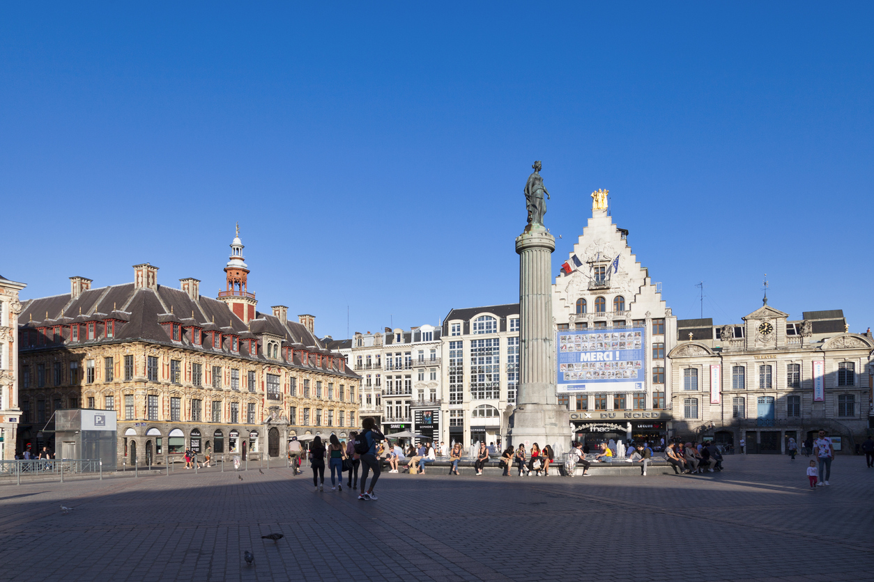 Lille, France - June 22 2020: The Grand Place with the Old Stock Exchange (Vieille Bourse), the Column of the Goddess (Colonne de la Déesse), the building of the newspaper La Voix du Nord and the North theater (Théâtre du Nord).